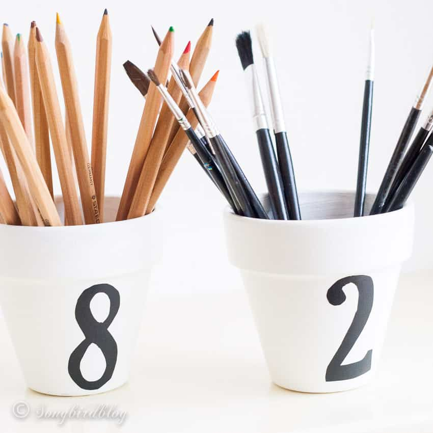 Two white containers with numbers containing pencils and brushes