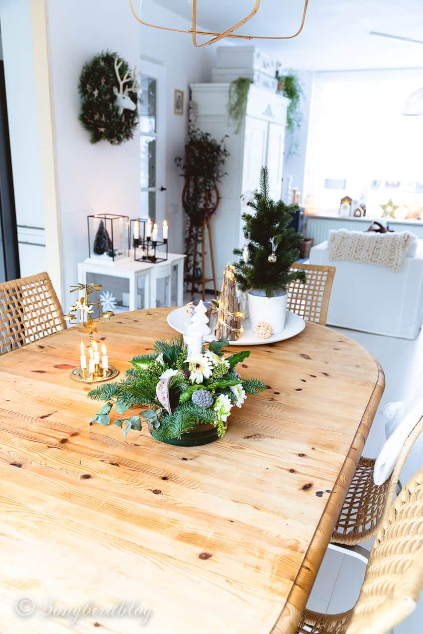 Pine dining table decorated for Christmas in white interior.