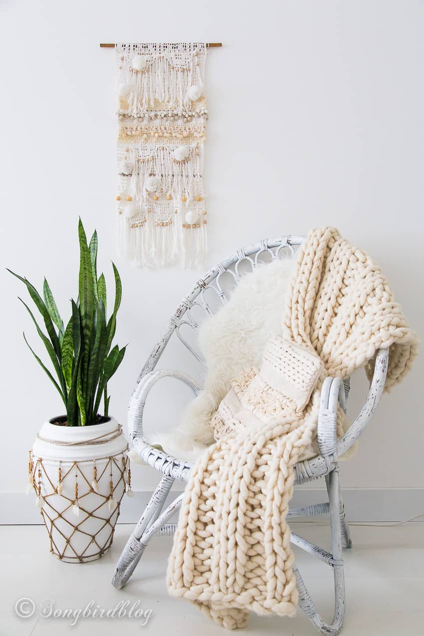 white interior bohemian style wall hanging and wicker chair