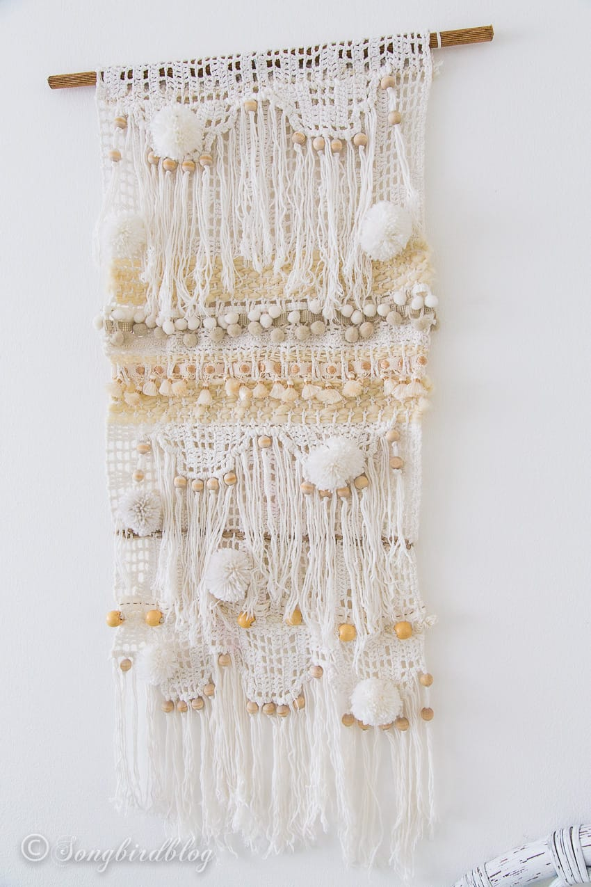 homemade yarn wall hanging with pompoms and fringe