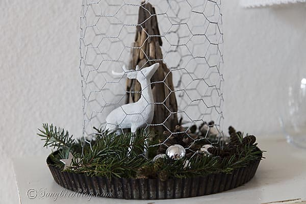 Rustic Christmas decoration with a driftwood Christmas tree and a painted deer under a chicken wire cloche. http:www.songbirdblog.com