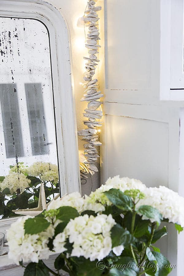 driftwood garland with a string of lights and shells