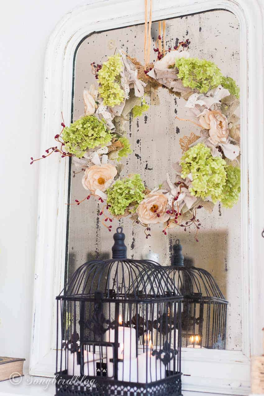 floral fall wreath on vintage mirror with bird cage decor