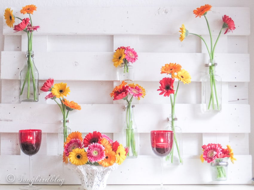 Rustic pallet wood mantel with flowers in bold colors