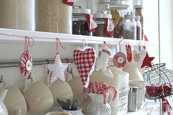 red and white christmas in the kitchen with a fabric ornament garland