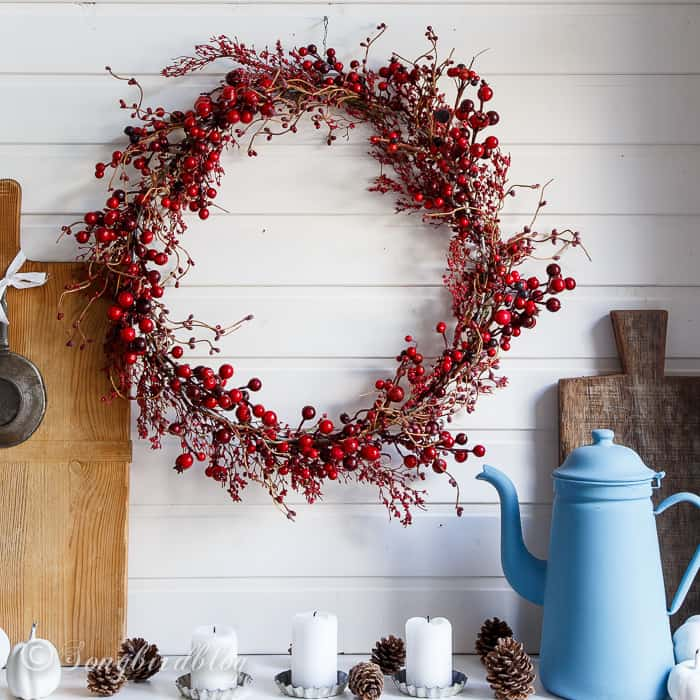 farmhouse Fall mantel decor with a red berries wreath