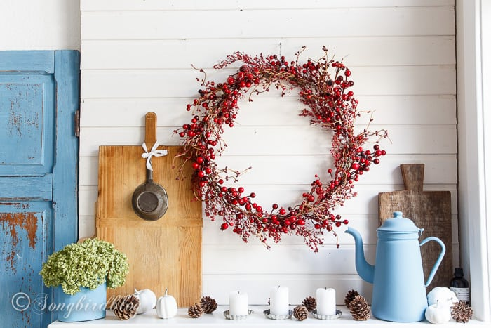 farmhouse Fall mantel decor with a red berries wreath and vintage kitchen items