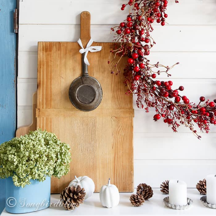farmhouse Fall mantel decor with vintage kitchen items like a bread board and cake tins as candle holders