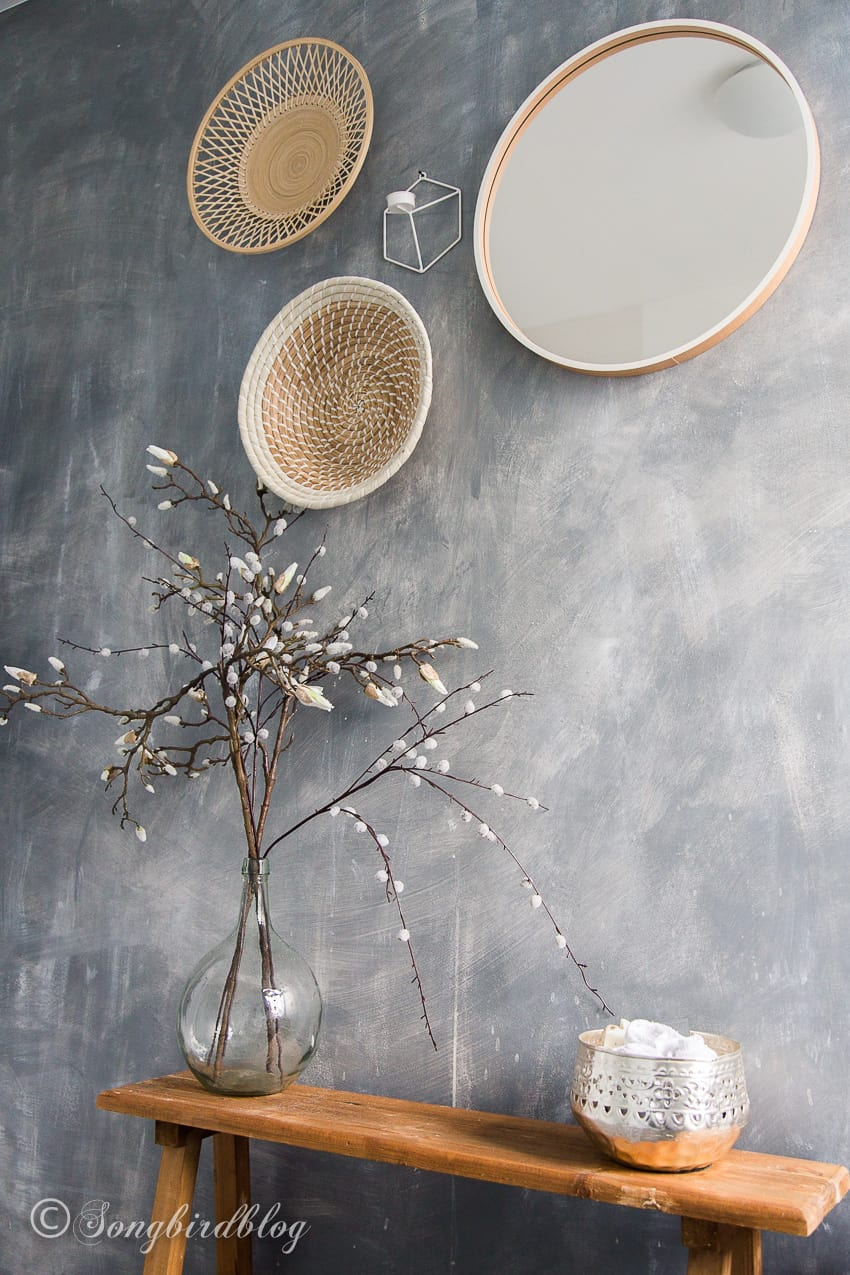 grey painted faux concrete wall with round baskets and mirror