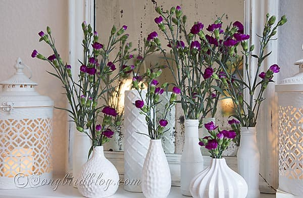 Mantel decoration with a group of white vases with pink flowers in front of a vintage mirror. Songbirdblog.com