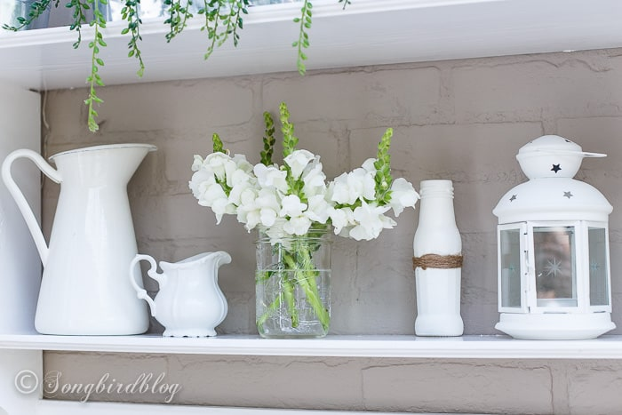 Outdoor decorating on a white shelf with lots of white flowers.
