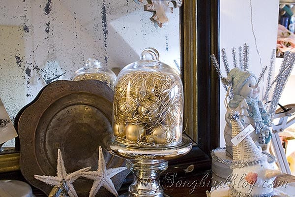 glass cloche filled with tinsel and Christmas balls