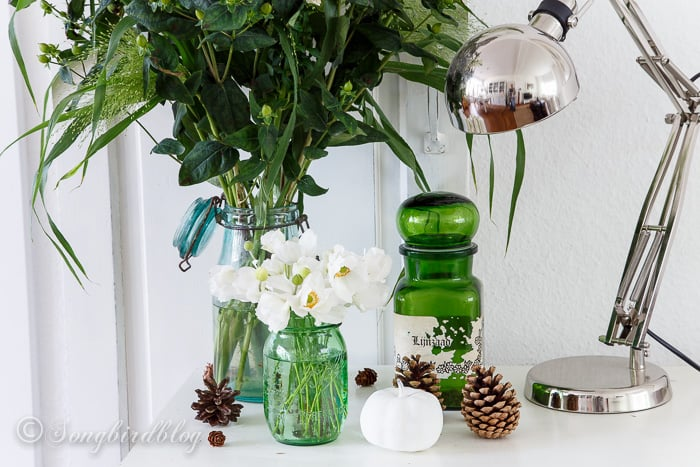 Fall arrangement in green with a vintage medicine jar, white flowers and of course with pine cones.