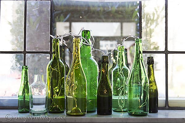 I love this easy and fun window sill decoration. Re-purpose some old green bottles, add a string of lights and a quick and lovely display is born. See it at http://www.songbirdblog.com