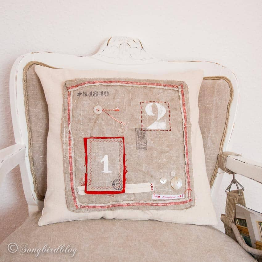 handmade pillow in neutral colors with red accents and numbers