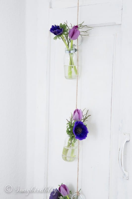 small bottles hanging on twine with purple flowers