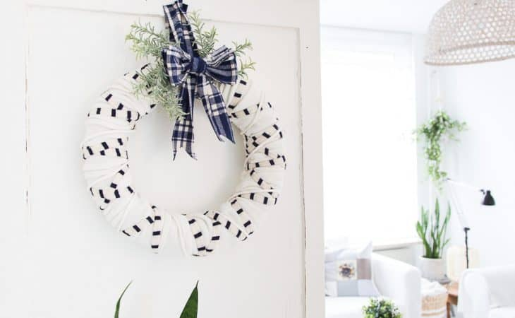 White living room with winter scarf wreath hanging on a wall