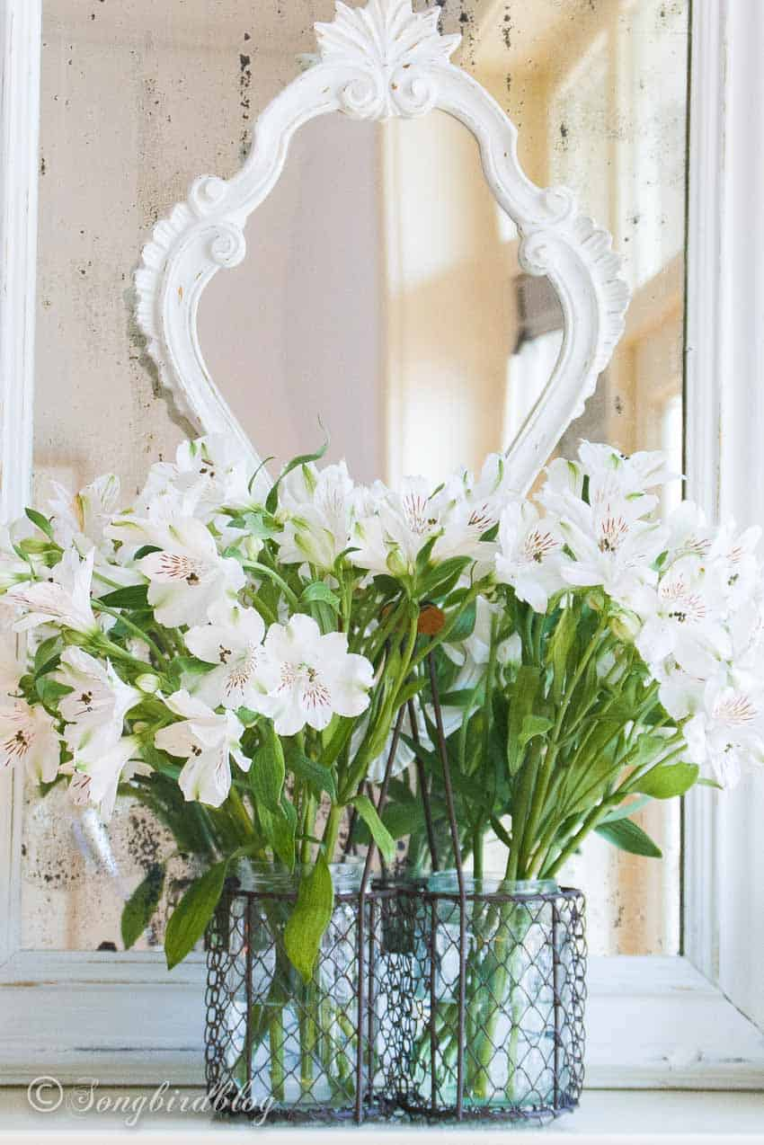 Two white layered mirrors with a bouquet of white flowers in front