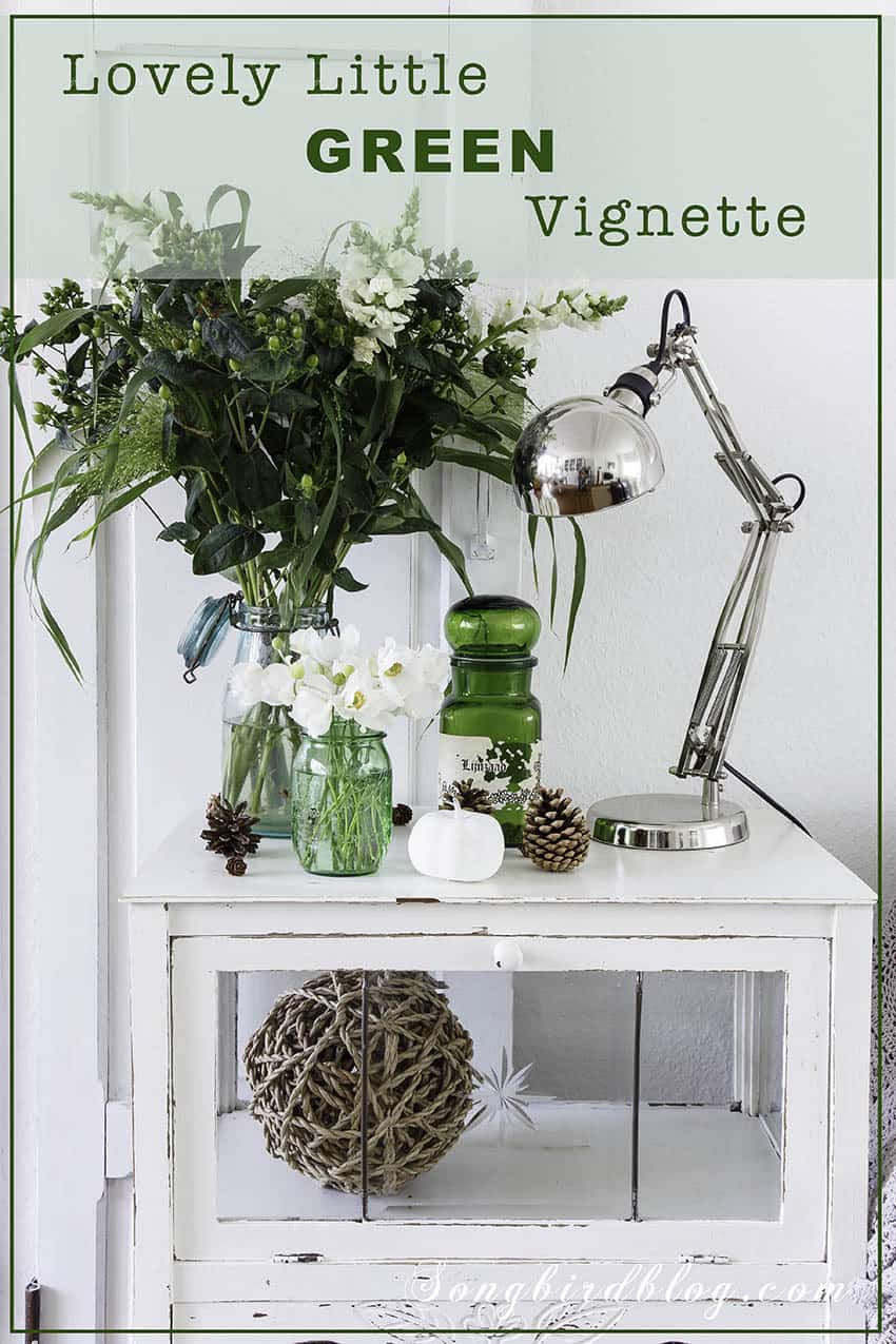 Decorative display with green vases and flowers on a with side table