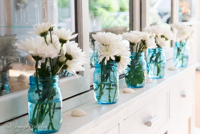 nautical home decor with a blue mason jars and flowers