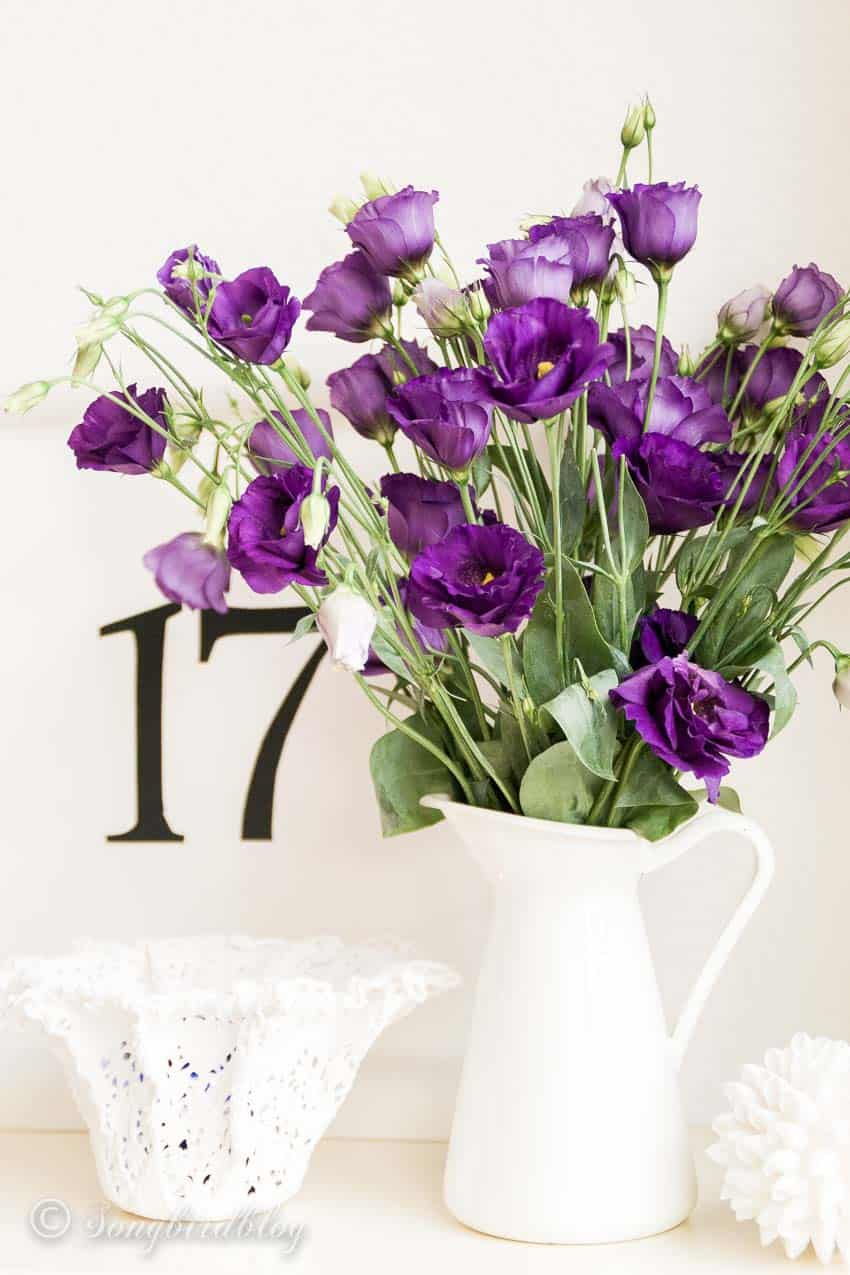 white painted tray with black number and a white pitcher with purple flowers