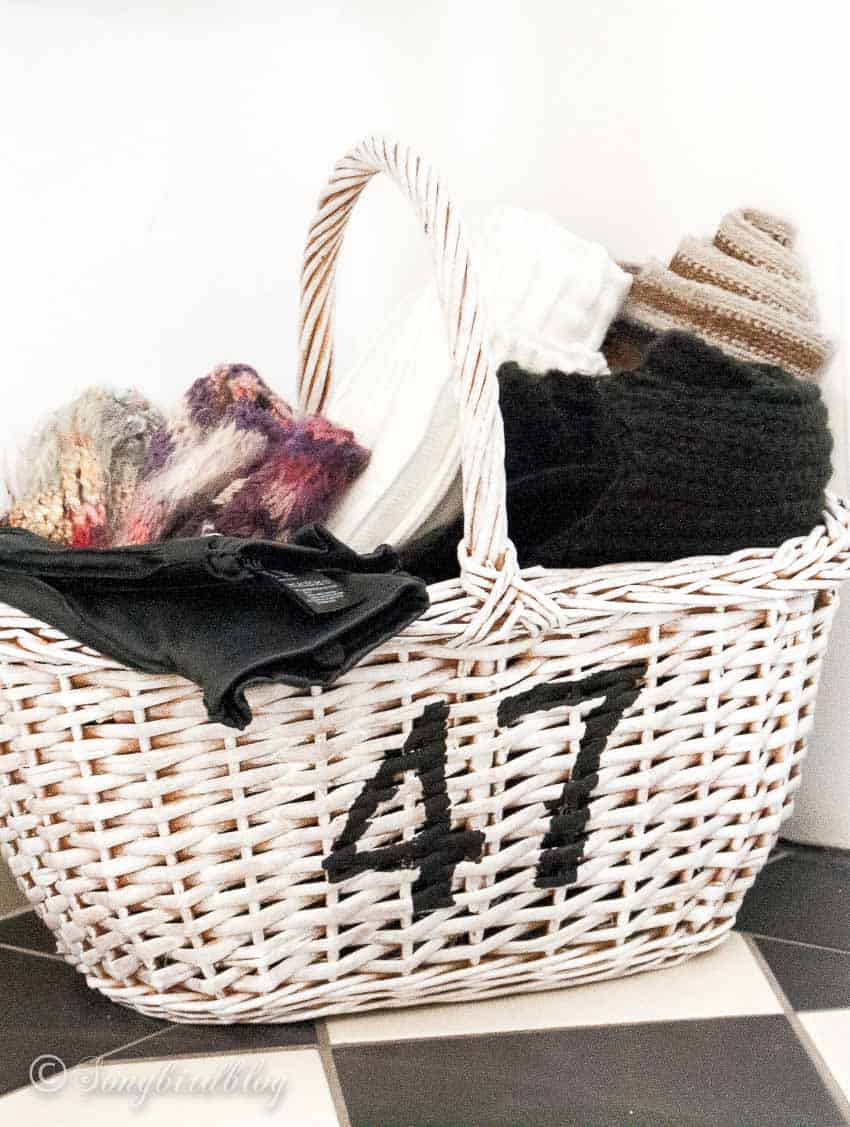 white painted numbered basket with winter scarfs