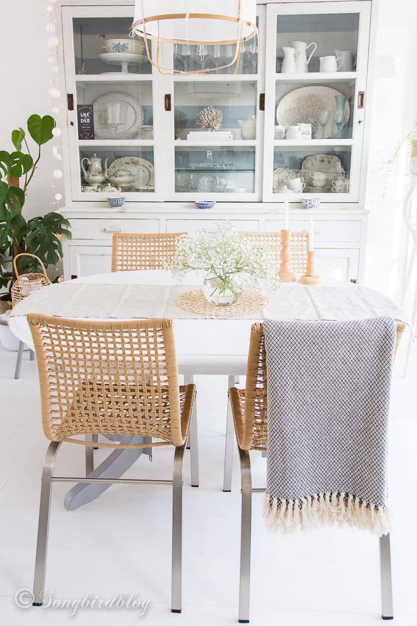 white dining table with four rattan chairs