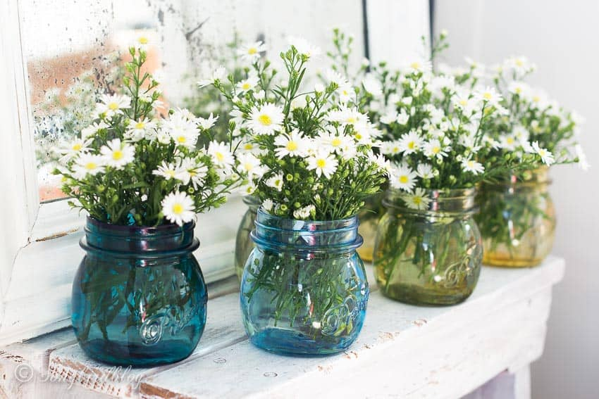 Ombre colored green glass jars with flowers on a bench
