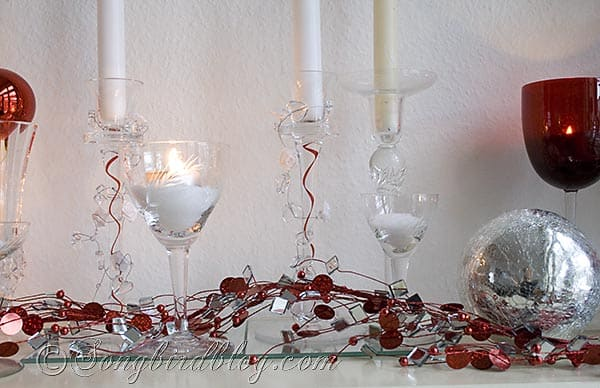 glass candle sticks and silver and red decorations on a mantel for Christmas