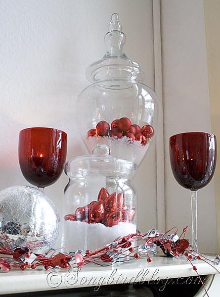 glass containers with snow and red Christmas ornaments