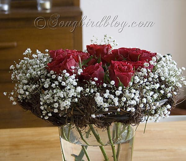 exposed stems bouquet with red roses in a wreath
