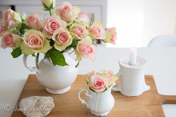 In this little roses centerpiece idea I split one bouquet in two and arranged them in some white crockery and paired them with a vintage bread board.