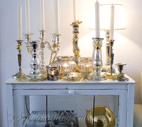 cupboard decorated with silver candle sticks and gold ornaments for Christmas