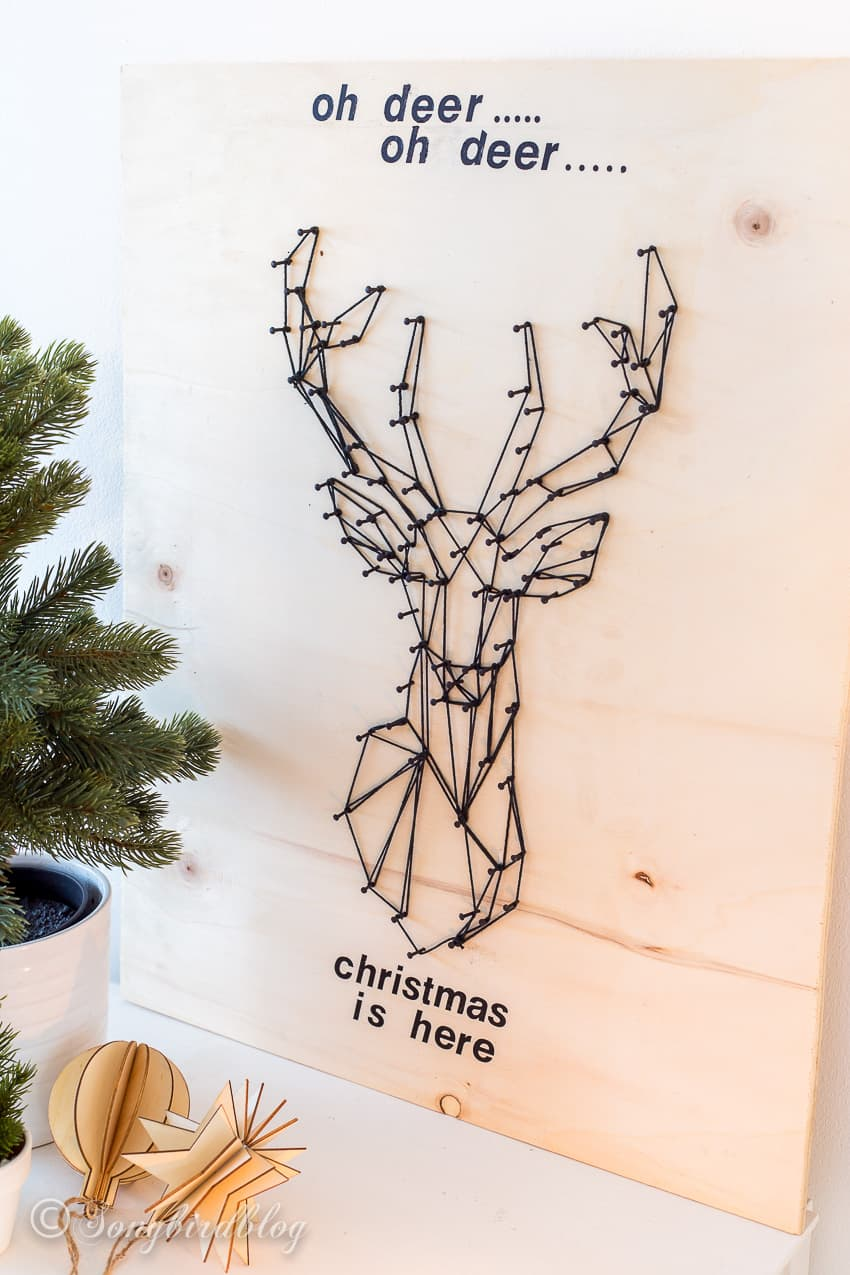 deer head string art Christmas decor with black string on light wood