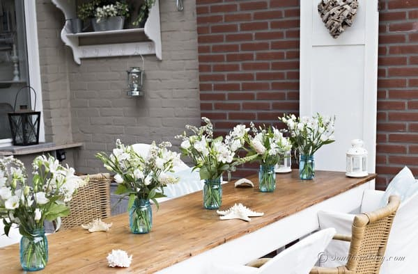 A line up of blue mason jars with bouquets of randomly chosen white flowers. Just perfect for a wedding table setting.