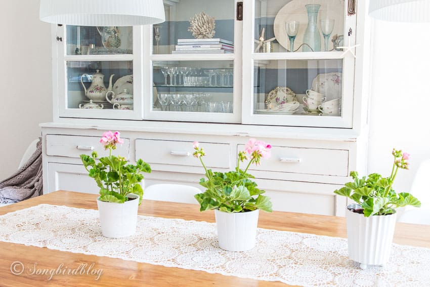 Row of pink flowers on dining table in front of white hutch