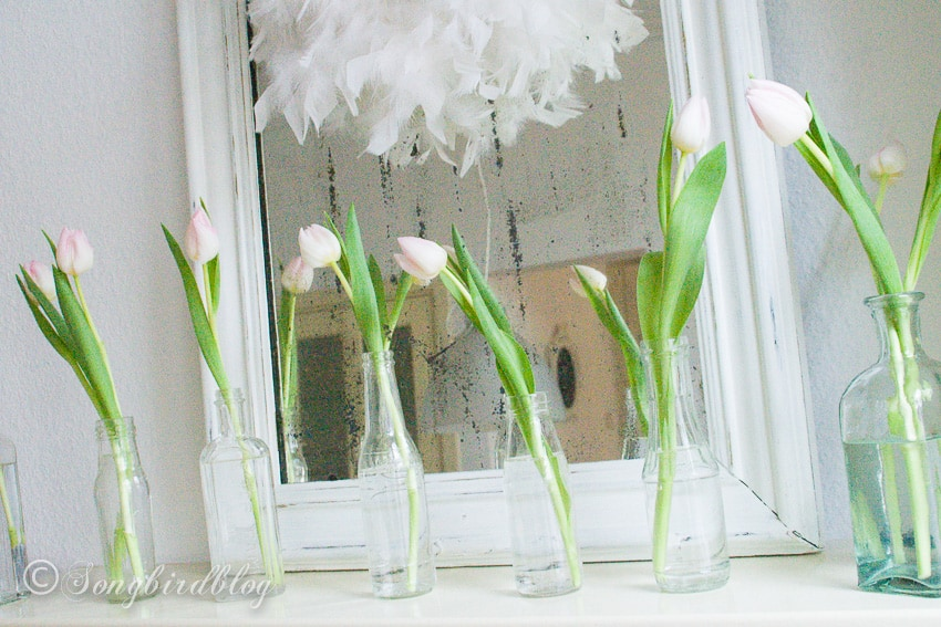 Mantel decoration with pink tulips in vintage bottles