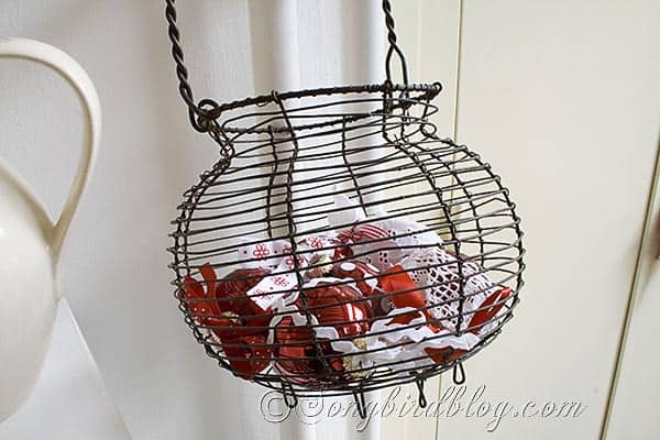 wire basket with red and white Christmas ornaments in kitchen