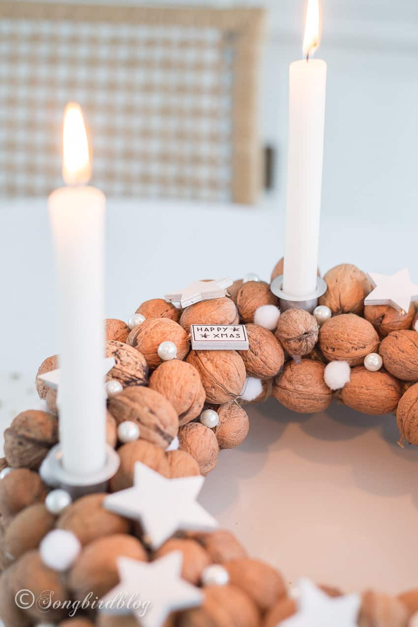 Walnut wreath Christmas centerpiece on white table with burning candles