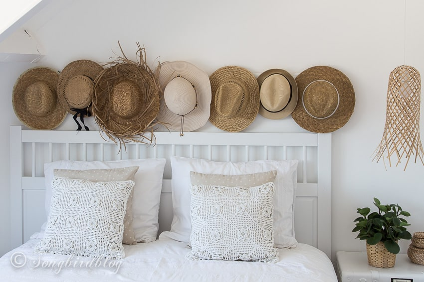 a line of straw hats decor in white boho bedroom