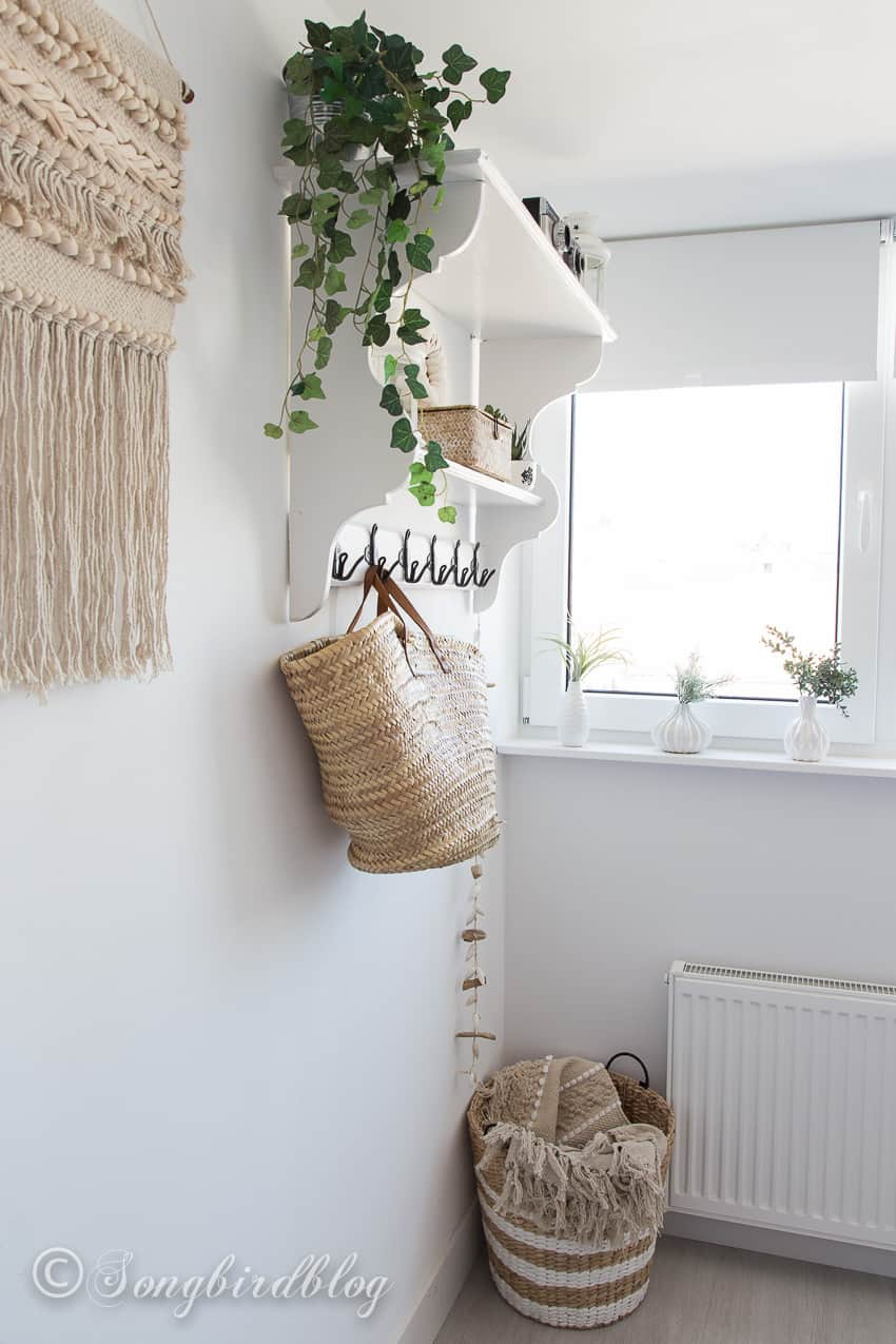 wall shelf and neutral colored accessories in a white boho bedroom