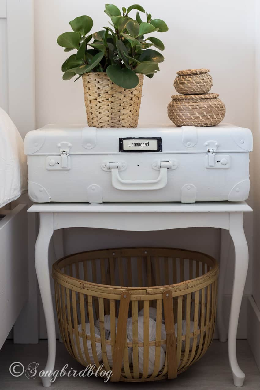 white suitcase nightstand in boho bedroom
