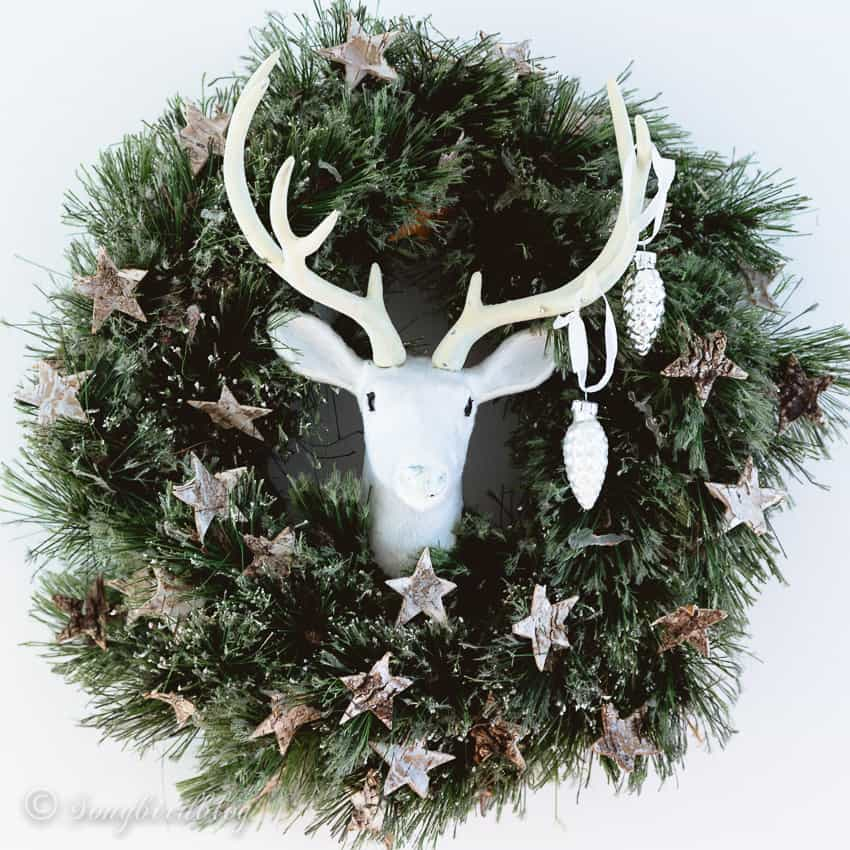 green wreath with bark stars and a deer head Christmas decoration