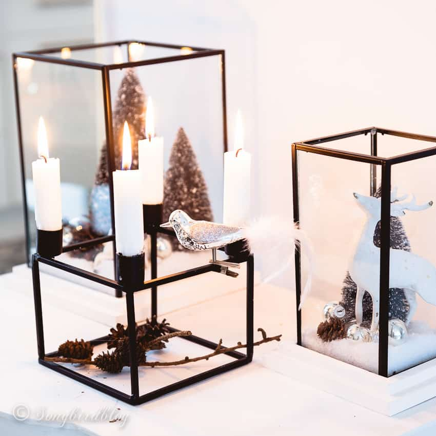 two glas lanterns filled with Christmas decor behind a square four candles candle holder
