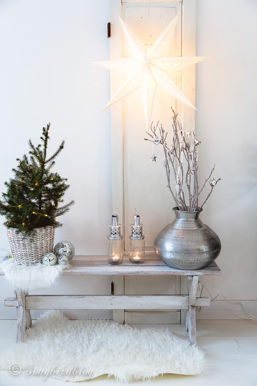 white and silver christmas decorations with a mini christmas tree on a white vintage bench