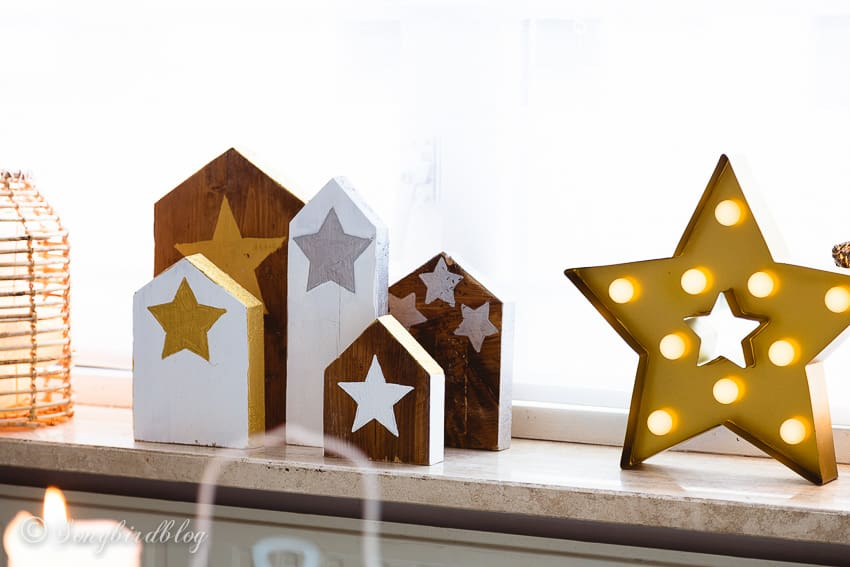 Christmas decorations of painted wood houses with stars and a golden star lamp on a window sill