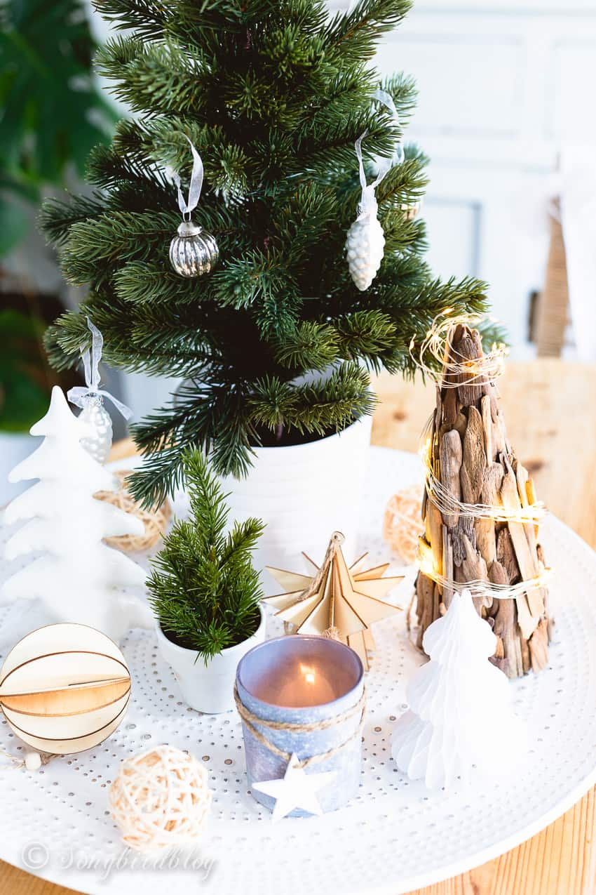 Christmas centerpiece of a white tray with christmas ornaments, candles and little christmas trees