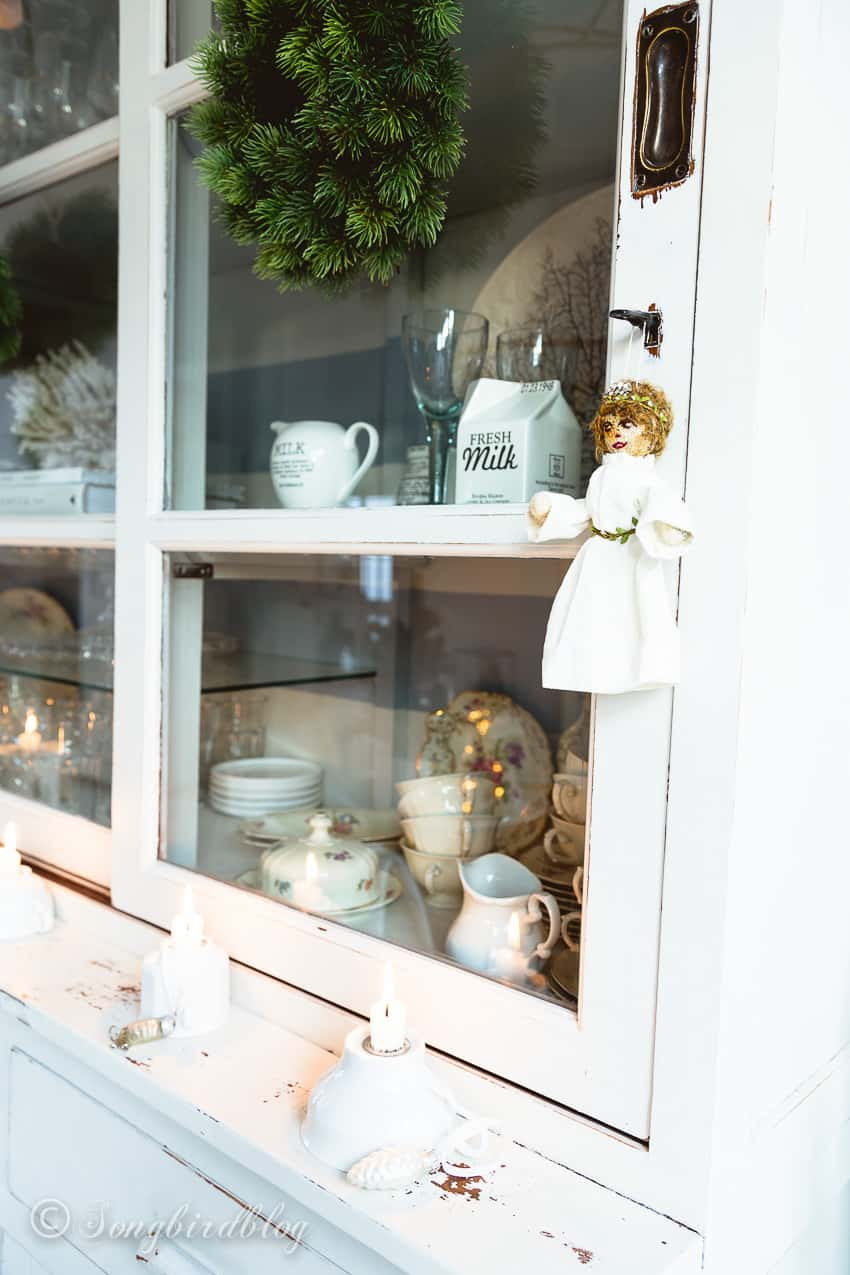 white painted dining room hutch with candle sticks and a homemade angel hanging from the key