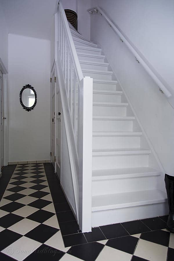 white painted staircase in black and white hallway