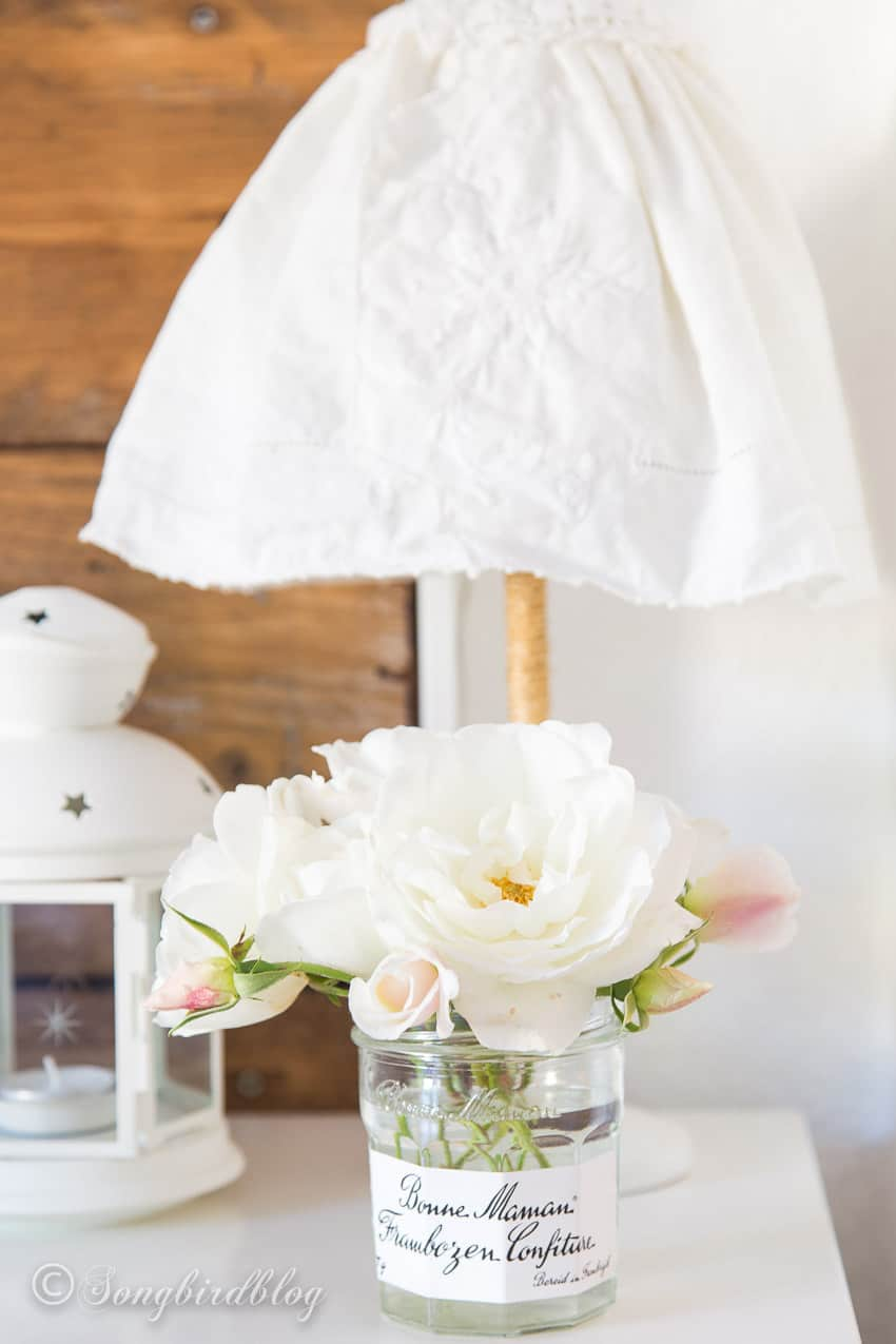 bedroom with reclaimed wood headboard and bedside table with vintage lamp shade and white roses